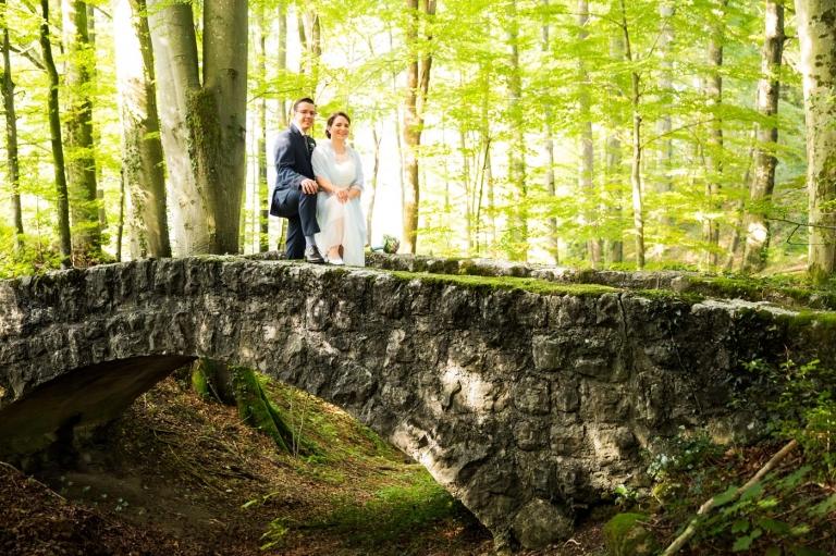 Hochzeitsfotos mit Portraits des Brautpaars im Wald auf einer steinernen Brücke aus Steinen in der Natur