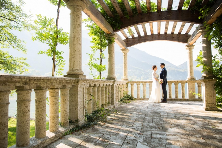 Hochzeitsfoto Brautpaar romantischer Säulengang in den Bergen mit Efeu und Sonne Gardasee Kochelsee München